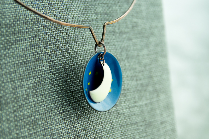 Moon and starry sky celestial pendant created in torch fired enamel, suspended from a hand forged patina copper neck wire