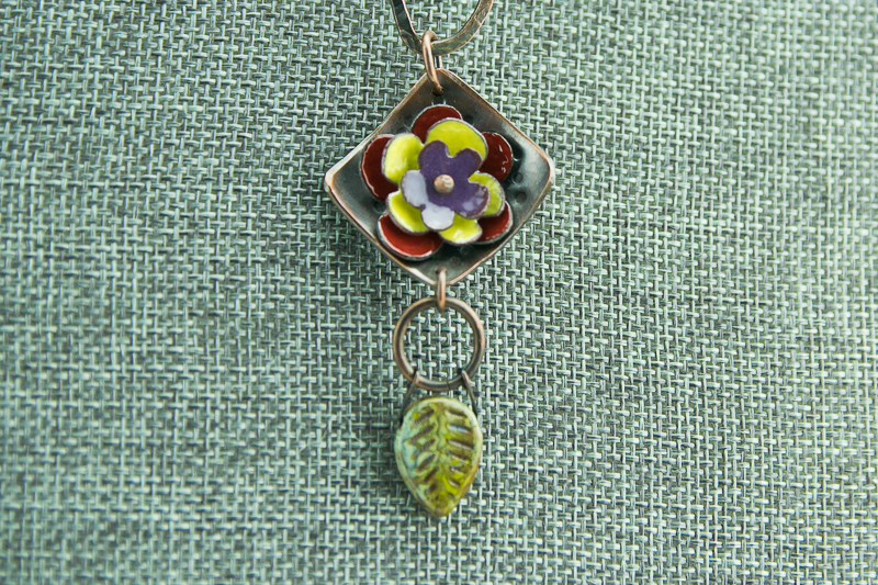 Patina copper and torch fired enamel flower pendant with Czech glass leaf dangle