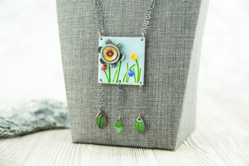 A square enamel pendant with garden motif and leaf dangles on a handmade patina copper chain