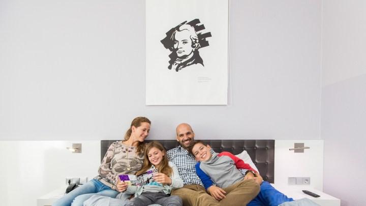 Eine Familie liegt in einem Hotelbett unter einem modernen Lessingbild