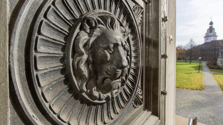 Mit Blick über den Löwen an der Tür der Bibliothek sieht man im Hintergrund das Schloss