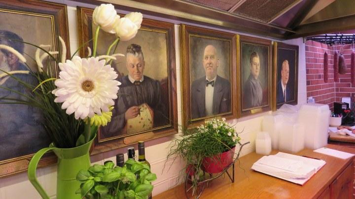 Im Verkaufsraum hängt eine Bildergalerie der Ahnen, die beim Tagesgeschäft zuschauen.