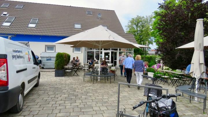 Die Außenterrasse der Wolfenbütteler Eismanufaktur mit vielen Sitzbänke und großen Sonnenschirmen.