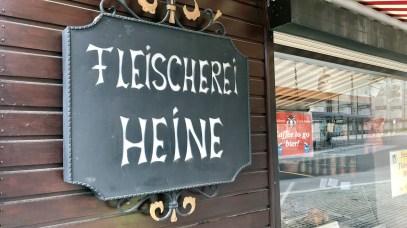 """Neben dem Eingang hängt ein altes Schild auf dem """"Fleischerei Heine"""" steht."""