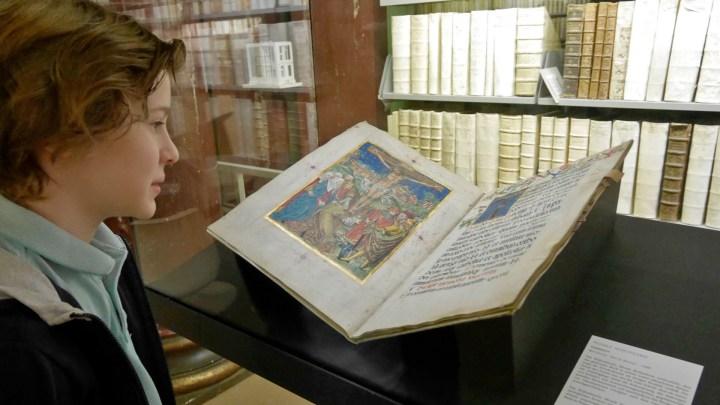 Ein Kind betrachtet ein aufgeschlagenes, altes Buch mit Handschrift und farbiger Malerei. Im Hintergrund Bücherregale mit, in Leder eingebundenen, alten Büchern.