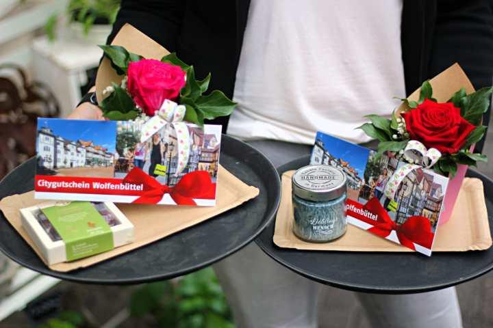 Der Citygutschein Wolfenbüttel präsentiert sich mit einem Blumenstrauß, einer Pralinenschachtel oder einer Kerze zum Muttertag