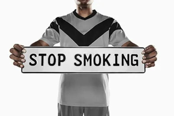 Man holding Stop Smoking Sign - ecigarettenews.net