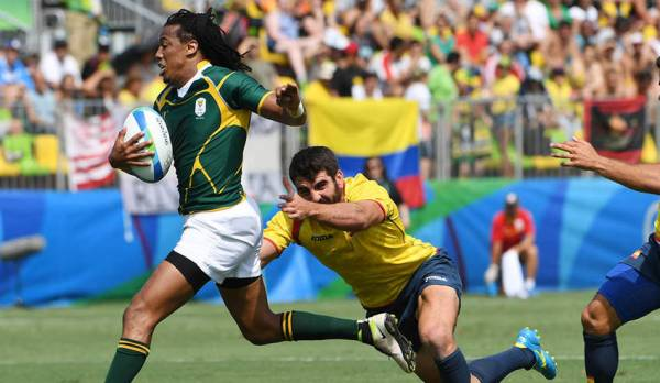 A South African player avoids a tackle by a player from Spain.