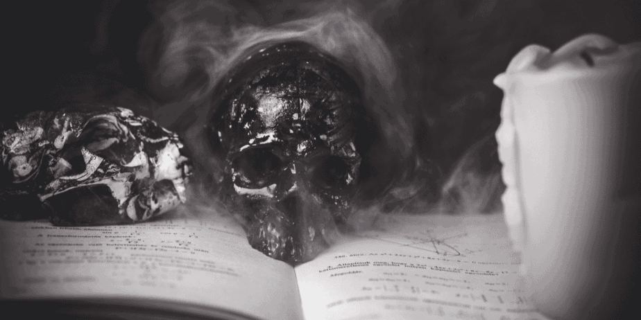 A smoking skull and candle on a book in black and white