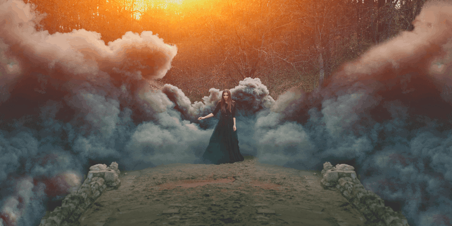 A witchy woman dressed in black surrounded by dark fog or smoke