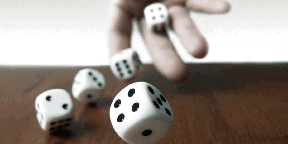 A hand throwing black and white dice on a wooden table