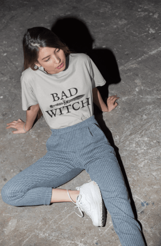 Woman wearing a Bad Witch Dagger shirt and laying on a cement ground