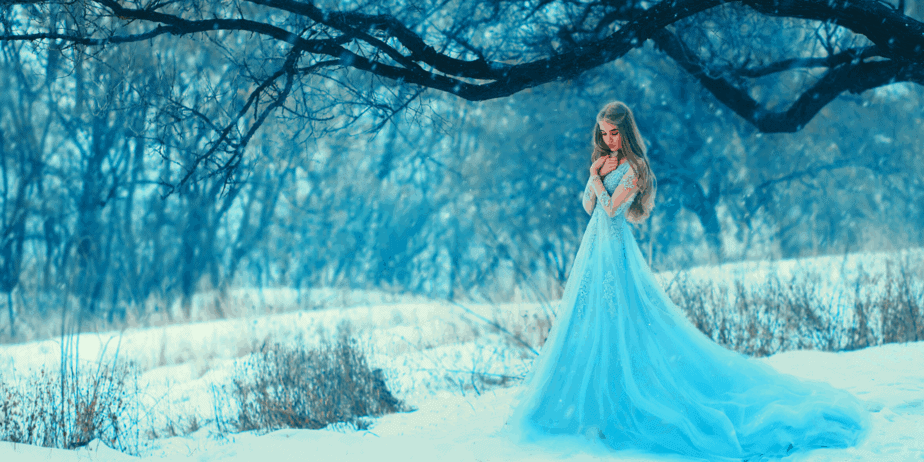 A witch in a white dress standing in the snow