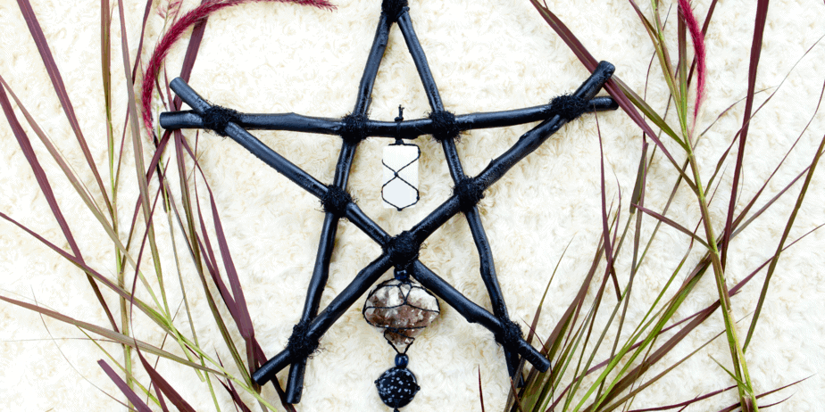 Black pentacle with crystals and leaves on a white wall