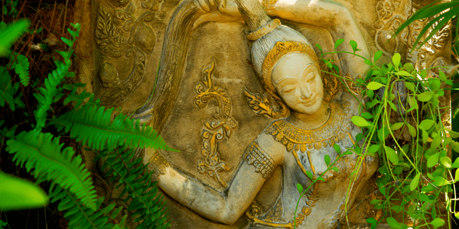 A carved relief of a goddess surrounded by greenery