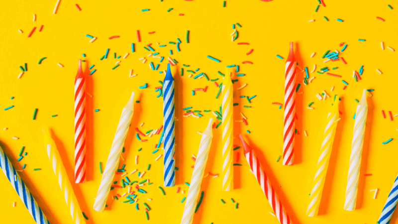 Decorative image of birthday candles and confetti on a yellow table