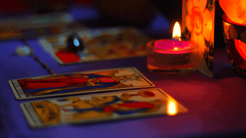 Decorative image of tarot cards laid out on a table with candles and crystals