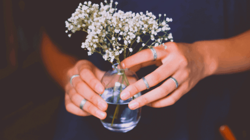 Decorative image of a woman with many rings on her fingers holding baby's breath flowers in a small jar filled with water