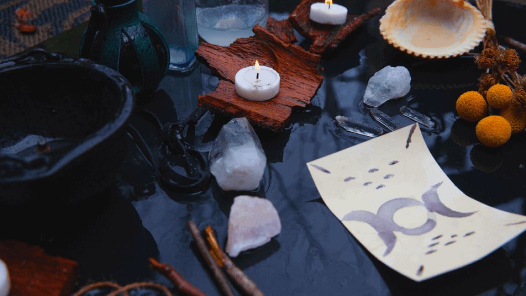 Decorative image of a pagan altar outside, wet from rain, with a drawing of the triple moon, a lit candle, a cast iron cauldron, and more
