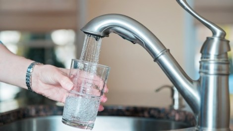 Hand holding a glass under a running tap, to avoid bottled water