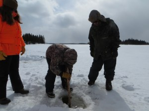 Students use a Y shapes stick to push a long floating stick to the next hole in the ice. The Stick has rope attacted to it which will then be attached to a gillnet and pulled out of the water, setting the net.