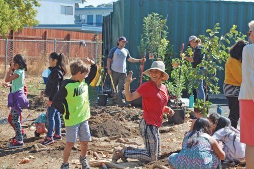 children and adults gardening in a community garden