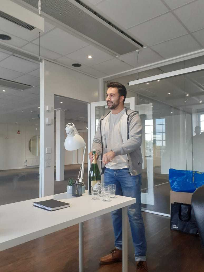 hamza opens champagne in the new ecobloom office