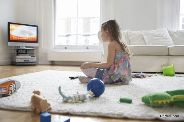 Girl Watching TV With Toys On Floor