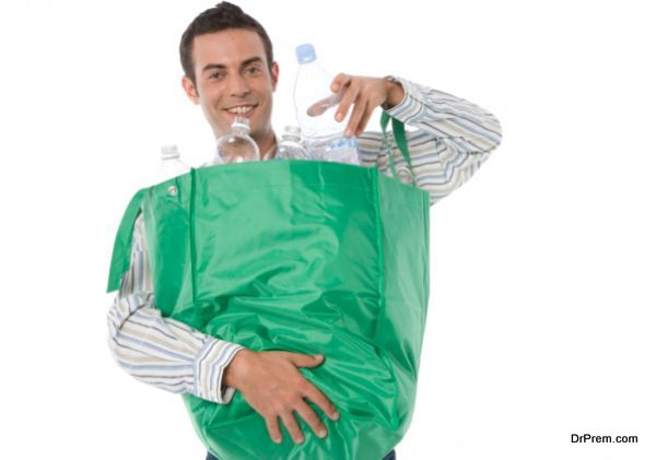 Young man holding a bag of plastic bottles for recycling