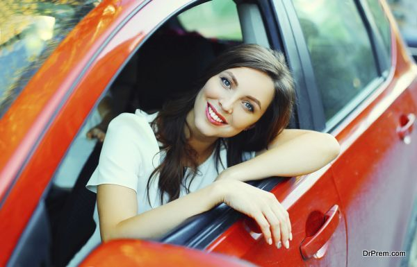 Beautiful smiling woman driver behind the wheel red car