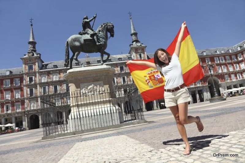 Madrid woman tourist on Plaza Mayor screaming with Spain flag.
