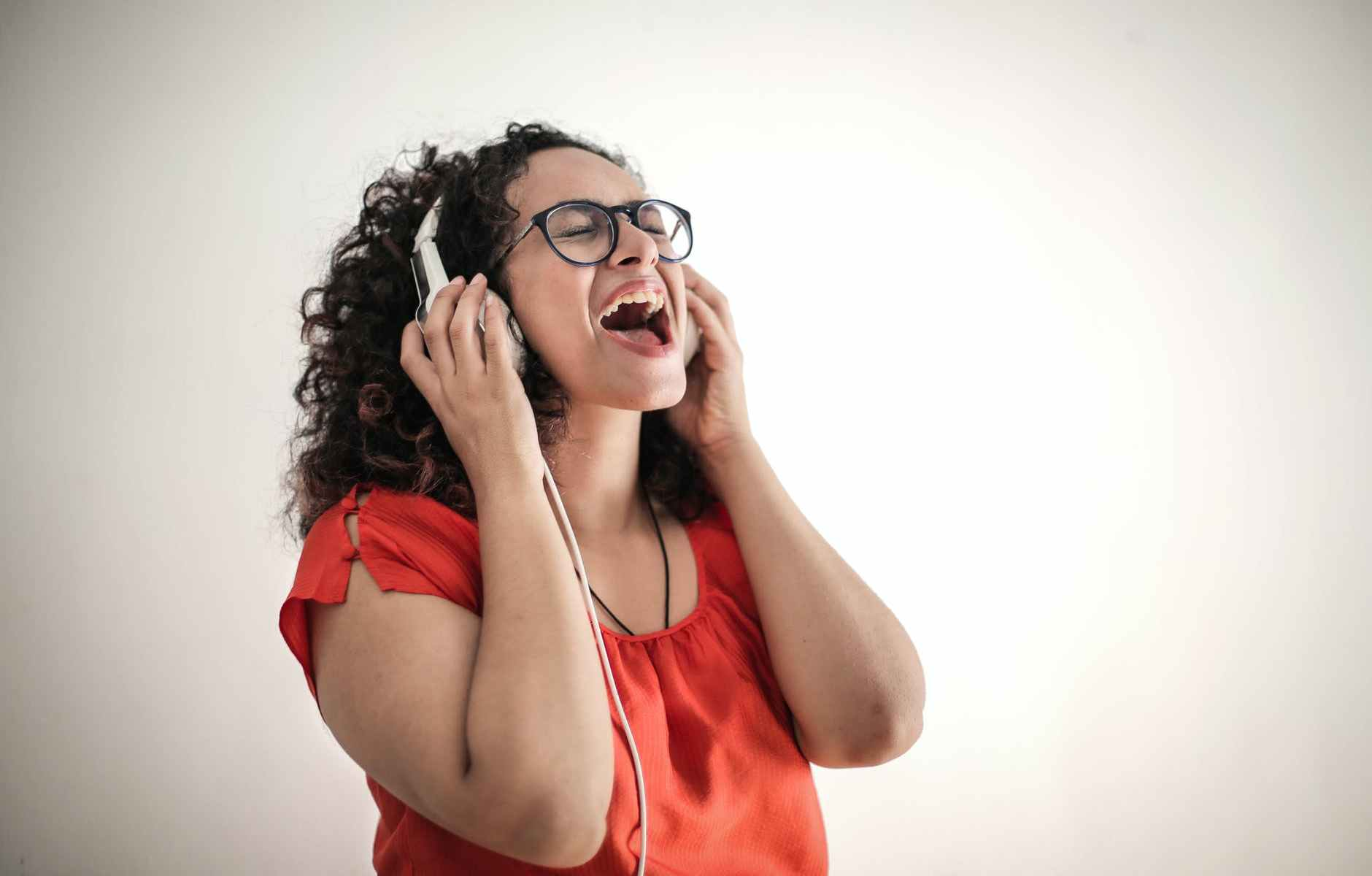 photo of singing woman in red top and black framed eyeglasses listening to music on her headphones