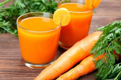 Glasses of carrot juice with vegetables on table close up