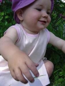 smiling toddler reaching towards camera, wearing pink and white striped pinafore dress and pink hat