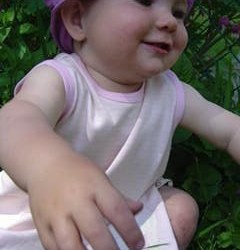 smiling toddler reaching towards camera, wearing pink and white striped pinafore dress and pink hat