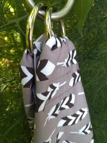 Close up of cotton midwifery weigh sling against green plants, pattern of grey-tan with all over pattern of white and black stylized feathers.