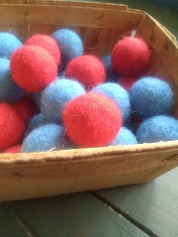 wooden basket filled with blue and red felted balls