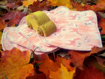 6 pack of peach coloured flannel washies with deers and trees pattern, lying among bright autumn maple leaves