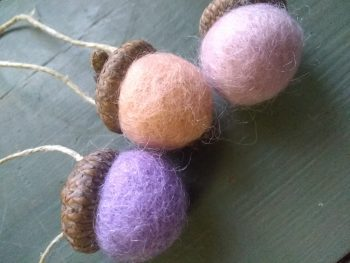 trio of felted wool ball ornaments with acorn caps, 1 mauve, 1 peach, 1 light pink