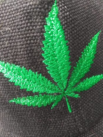 embroidery detail of black hemp canvas ball cap with bright green hemp leaf embroidered on front.