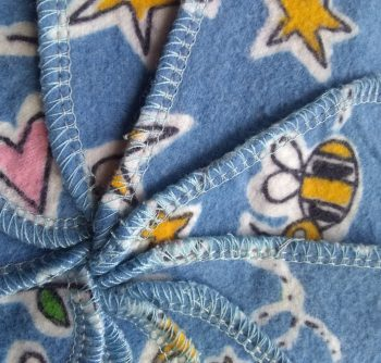 spiral made from serged squares of blue flannel decorated with stars, bugs and hearts