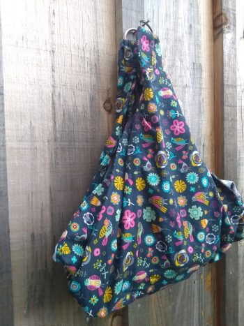 midwifery weigh sling from brightly folk pattern over dark blue background