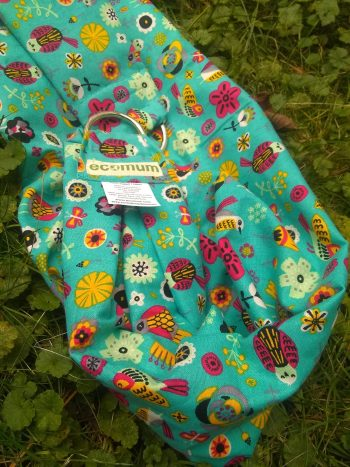 midwifery weigh sling from brightly folk pattern over bright blue background