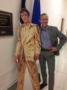 posing next to cardboard cutout of Elvis in a gold suit