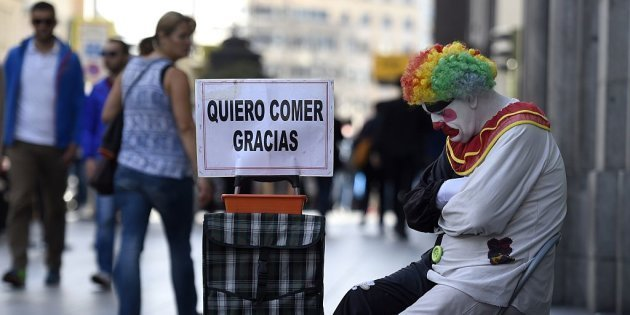 """Rayito, a beggar dressed as a clown sits next to a placard reading """"I want to eat, thank you"""" in Gran Via street, in the centre of Madrid, on October 28, 2014.   AFP PHOTO/ GERARD JULIEN        (Photo credit should read GERARD JULIEN/AFP/Getty Images)"""