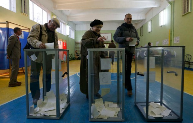 People cast their ballots during voting in a referendum at a polling station in Simferopol