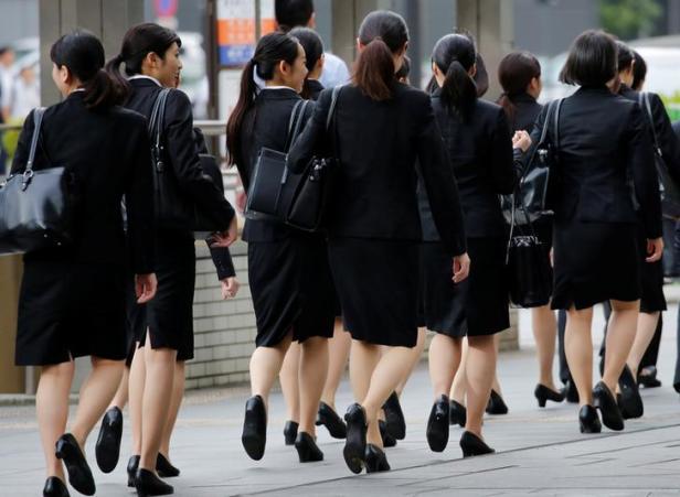 Des employés de bureau vêtus de talons hauts, de costumes et de sacs de la même couleur se promènent mardi dans un quartier des affaires de Tokyo. Photo: REUTERS