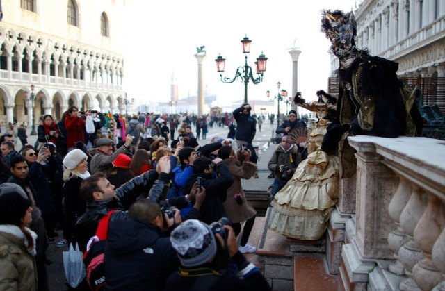 A couple, wearing costumes, poses at San Marco square during the Venice Carnival