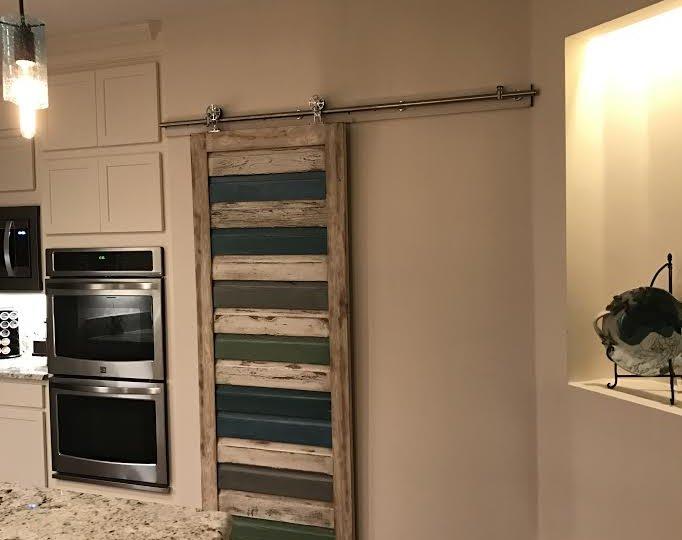 Beautifully hung custom barn door covering the pantry opening.