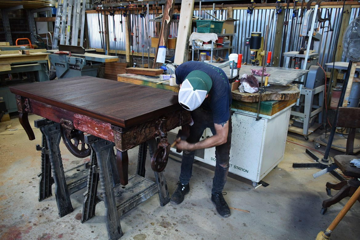 Billy applies the first coats of stain to the cart.